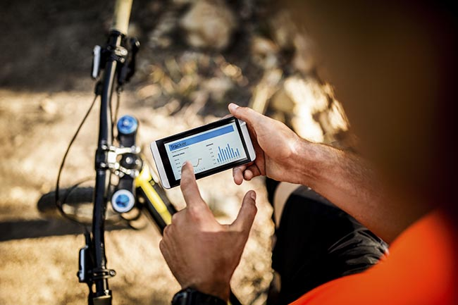 Mountain biker holding a smart phone with tracking app
